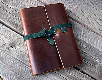 brown leather journal with green leather wrap strip